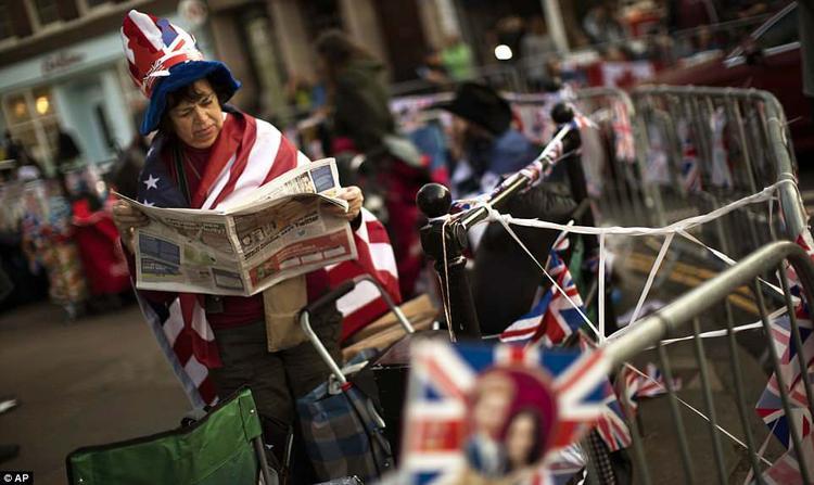 Một người phụ nữ quấn cờ quanh người đang đọc báo trong lúc chờ đợi. Ảnh AP