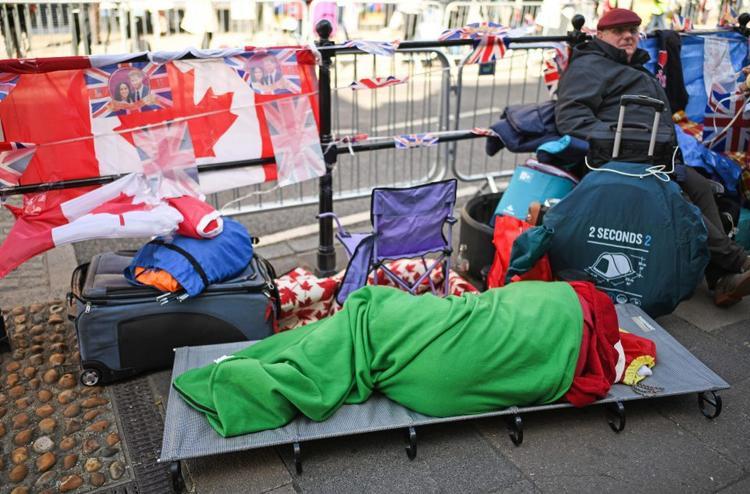 Một người phụ nữ nằm nghỉ ngơi trên giường gấp, bên cạnh là những chiếc vali chất đầy chăn gối và đồ ăn. Ảnh Getty Images