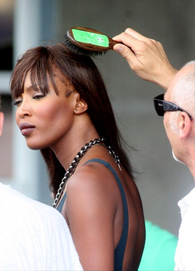 """Điển hình là """"báo đen"""" Naomi Campbell. Siêu mẫu gốc Bờ biển Ngà nhiều lần bị ống kính máy ảnh chộp được hình ảnh mái tóc trơ trụi, xơ xác và rụng rất nhiều. Cô thường phải chọn kiểu tóc ép hoặc sấy phồng để che khuyết điểm này mỗi khi xuất hiện trên thảm đỏ."""