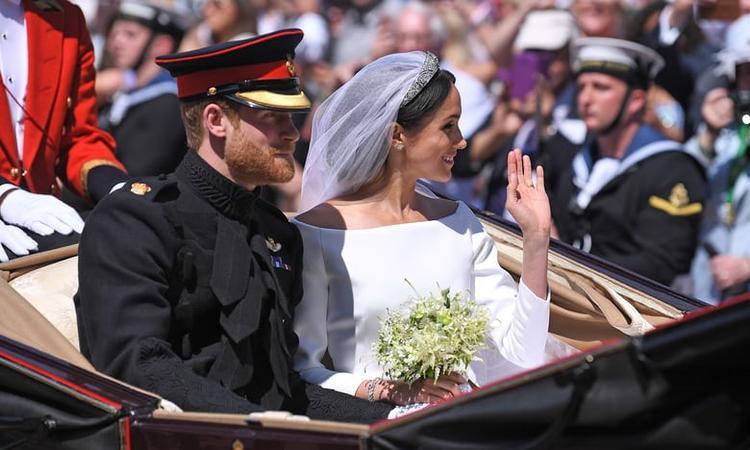 Hơn 100.000 người hâm mộ vẫy cờ chào đón và hô vang tên của Công tước và Nữ công tước xứ Sussex. Ảnh Reuters