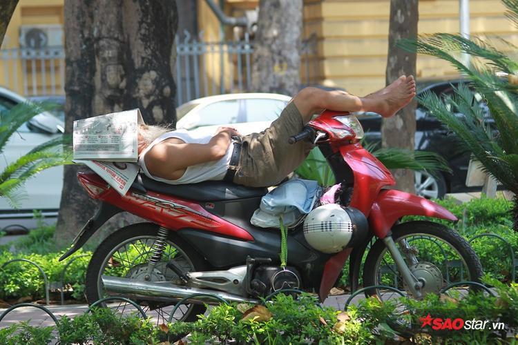 Bác xe ôm nằm ngủ ngay trên phương tiện chuyên dùng để kiếm cơm. Vật chống nắng duy nhất là một tờ báo úp lên mặt.