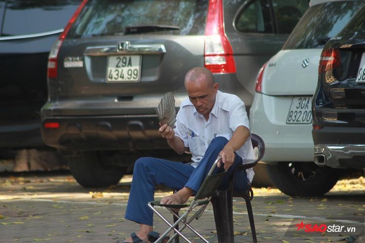 Bác bảo vệ trông xe phải làm việc xuyên trưa, không có nơi để ngủ, phải kê 2 chiếc ghế cạnh nhau, ngồi dưới bóng cây thư giãn.