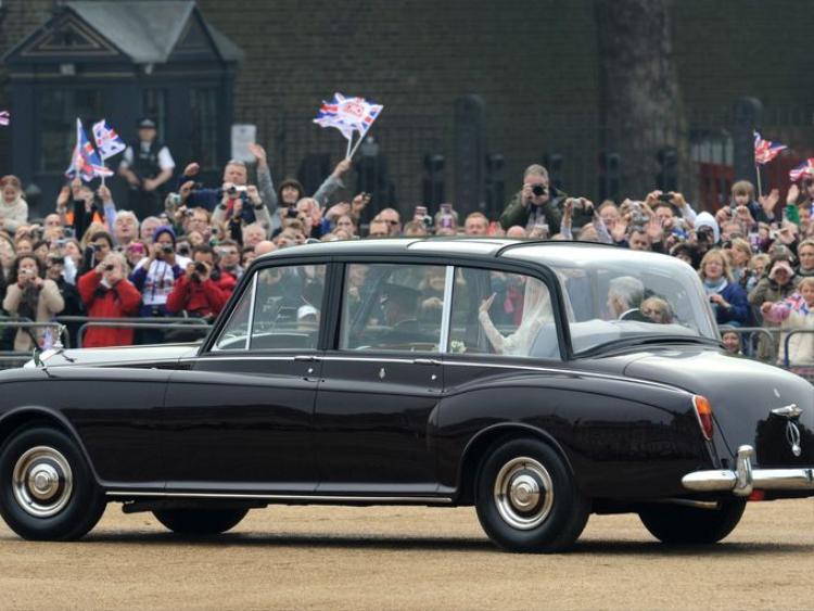 Kate Middleton vẫy chào khi di chuyển bằng chiếc Rolls Royce Phantom IV với cha mình Michael Middleton đến Tu viện Westminster ở London trong lễ cưới cùng Hoàng tử William vào ngày 29 tháng 4 năm 2011.