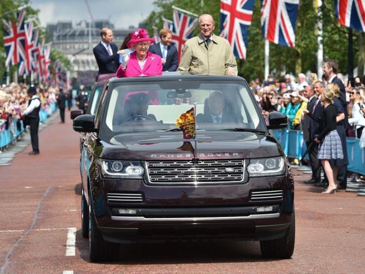 Nữ hoàng Elizabeth II và Hoàng thân Philip vẫy chào khách mời tới dự lễ sinh nhật lần thứ 90 của bà trên một chiếc Range Rover.