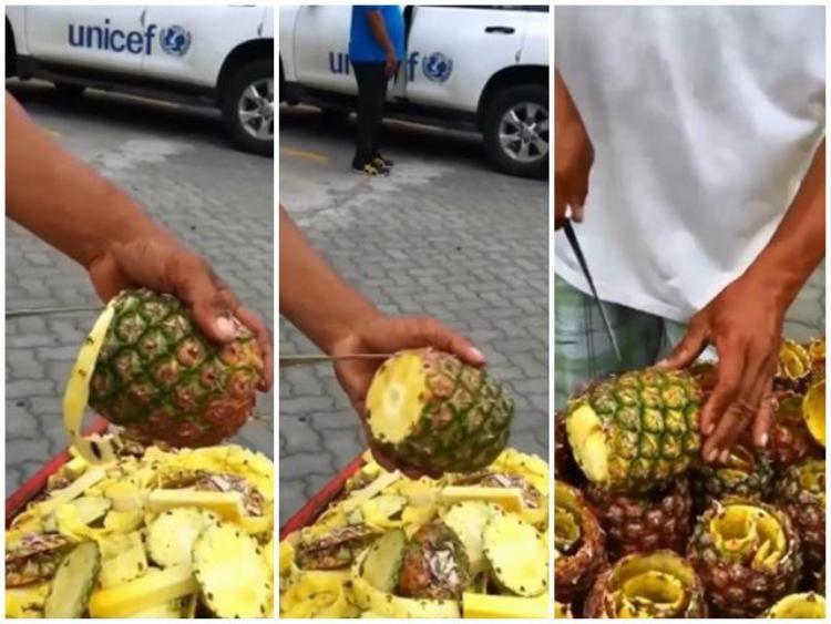 Một tay xoay quả dứa, một tay đưa dao cắt quanh quả dứa để tách riêng phần vỏ ra.