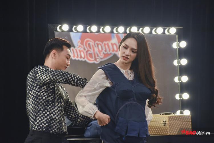 MC Thành Trung giúp Hương Giang khoác lên người chiếc áo bầu đặc biệt.