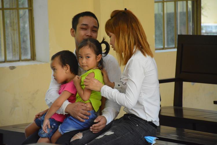Bị cáo Tiên ôm vợ con và khóc nức nở tại phiên tòa. Ảnh: Hồng Bằng
