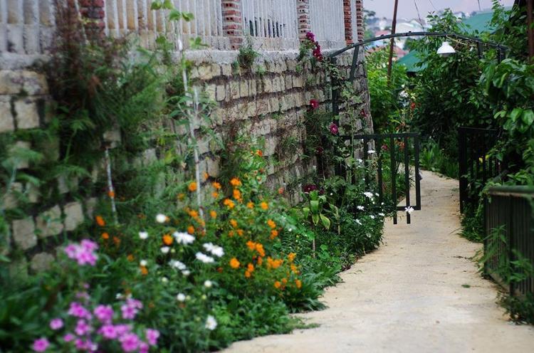 """Nằm nép mình giữa không gian chỉ toàn đồi núi, cây cỏ, Jang & Min hiện ra như ngôi nhà nhỏ trên thảo nguyên. Ngôi nhà ấy có lối vào phủ đầy hoa, có cánh cổng màu xanh cao chưa quá đầu, có view ngắm hoàng hôn và bình minh đẹp """"quên sầu"""". Những chi tiết nhỏ trong nhà đều được thiết kế xinh xắn. Ảnh: Jang & Min's house"""