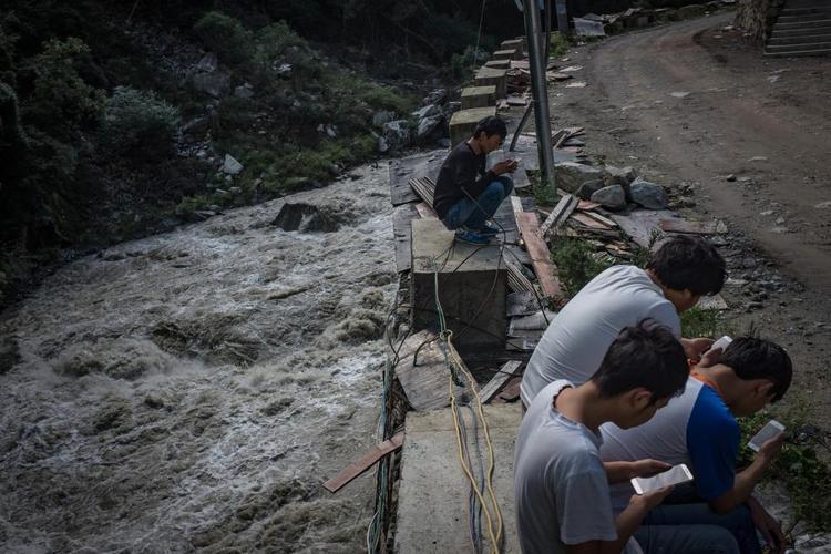 Thợ đào dùng điện thoại để chơi game và xem TV bên ngoài mỏ đào.