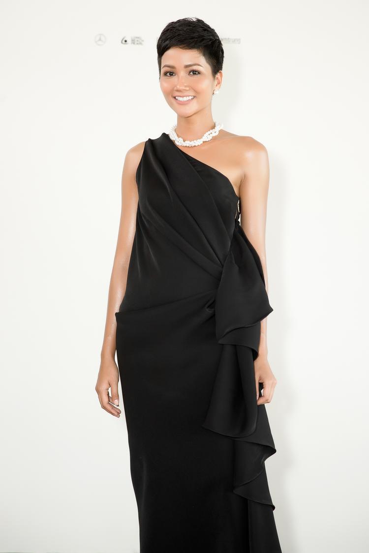 Hoa hậu Hoàn vũ Việt Nam 2017 H'Hen Niê diện chiếc đầm đen với thiết kế lệch vai, được tạo điểm nhấn bởi những đường gấp nếp bất đối xứng chạy dọc theo chiều dài thân váy. Người đẹp 9X kết hợp trang phục cùng vòng ngọc trai với tông màu trắng tương phản.