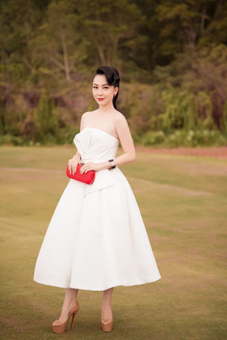 Nghệ sĩ múa Linh Nga khoe vai trần gợi cảm trong thiết kế thanh lịch, nữ tính với dáng xoè cúp ngực. Nữ nghệ sĩ chọn clutch màu đỏ đi kèm trang phục, vừa làm nổi bật món phụ kiện, vừa giúp trang phục thêm sức hút.