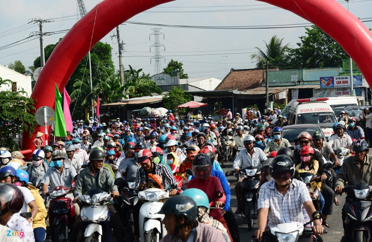 Đến 15h20, lực lượng chức năng mở rào chắn lối vào từ giao với quốc lộ 30, hàng nghìn người chạy xe máy, ôtô ào ào chạy vào đường dẫn lên cầu.