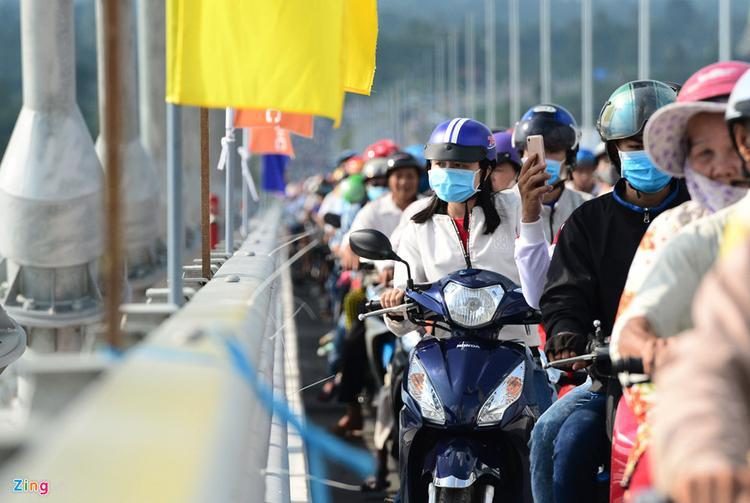 Dù xe cộ đông đúc, di chuyển chậm nhưng nhiều người vẫn cố gắng nhìn ngắm, chụp hình cây cầu dây văng, cảnh quan sông Tiền.