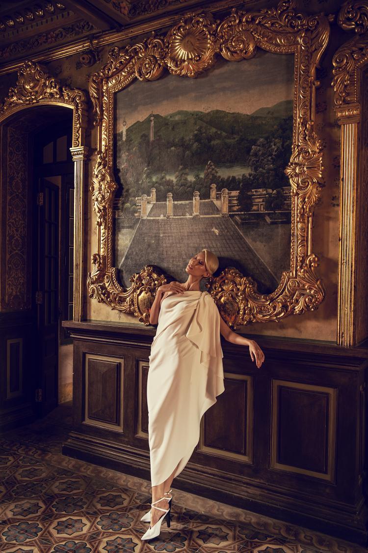 Với sắc trắng thanh lịch, Hằng Nguyễn diện thiết kế dáng dài với phần vai lệch gợi cảm kết hợp với những gấp, dún tập trung về một bên thân váy.