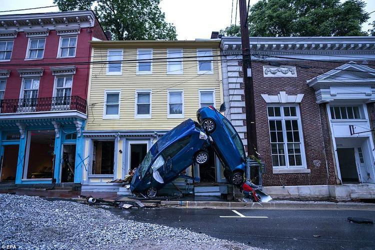 Hai chiếc xe nằm chỏng chơ trên đường sau khi trận lũ quét đi qua.