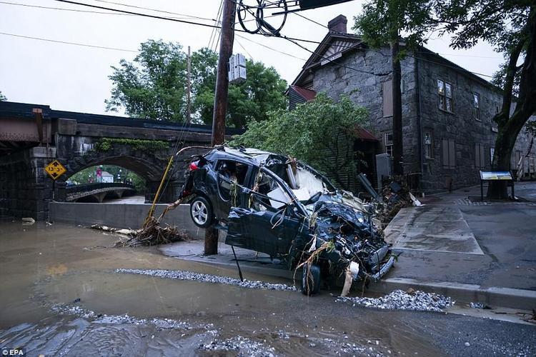 Một chiếc xe bị phá hủy nghiêm trọng, phủ đầy rác thải sau lũ quét.