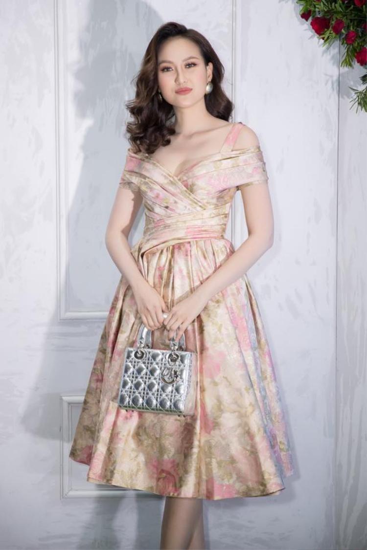 Khánh Ngân cũng mê mệt kiểu trang phục này, cô phối chiếc váy trễ vai cùng túi cầm tay ánh bạc của Dior.