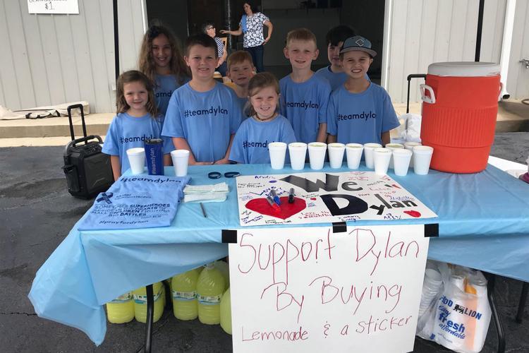 Cậu bé Andrew cùng các bạn bán nước chanh kiếm tiền giúp cha mẹ chữa bệnh cho em trai. Ảnh: AP