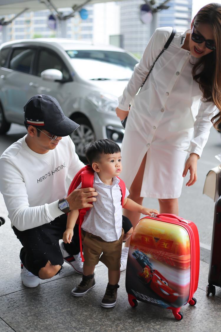 Nữ diễn viên diện váy sơ mi suông trắng trẻ trung, thoải mái cho chuyến bay dài. Ông xã Thanh Bình cũng mang đồ thể thao năng động hợp tông cùng vợ.