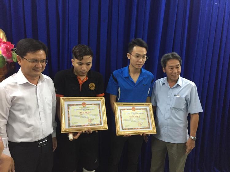 Chủ tịch quận khen thưởng các nạn nhân trong vụ bắt cướp. Nạn nhân Tiến (áo đen) và nạn nhân Quang (áo xanh).