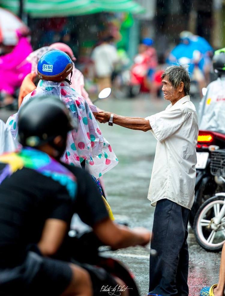 Cơn mưa ngày càng nặng hạt, người qua đường đều lướt qua, không ai để ý đến ông.