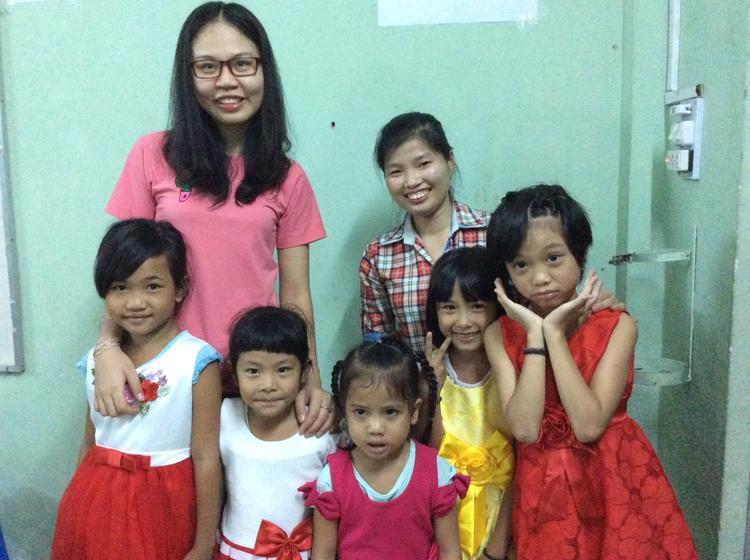 2 cựu sinh viên ĐH Nông Lâm (áo hồng và áo caro) trong buổi phát quần áo Tết cho các em nhỏ tại lớp học.