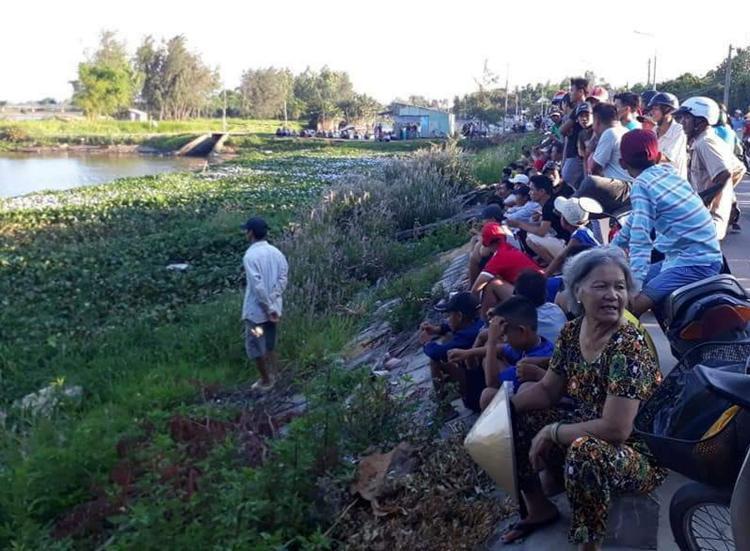 Hàng trăm người dân tập trung bên bờ sông Bàn Thạch để theo dõi việc tìm kiếm thi thể nạn nhân. Ảnh: CTV