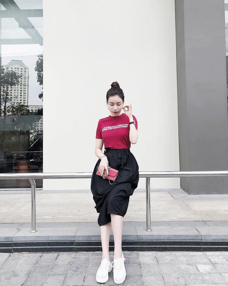 Hoa hậu Lam Cúc đem lại nét nữ tính, sang trọng cho chiếc áo thun basic khi phối nó cùng với chân váy và clutch cầm tay.