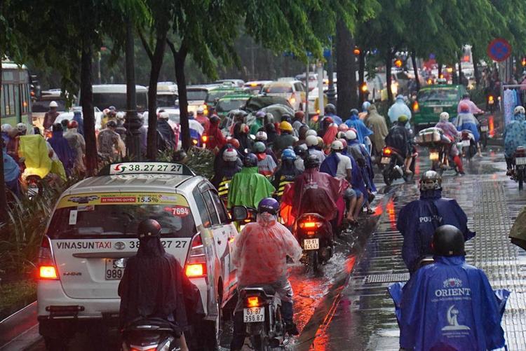 Xe ô tô, taxi phải len lỏi vào làn đường xe máy; trong khi đó, xe máy phải leo lên lề đường của tuyến phố Trần Quốc Hoàn. Ảnh: Vietnamnet