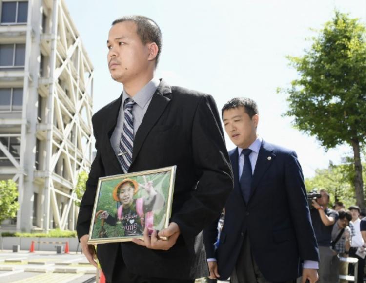 Bố của bé Nhật Linh, anh Lê Anh Hào, có mặt ở phiên tòa từ sáng sớm, trên tay cầm di ảnh của con gái. Ảnh: Kyodonews