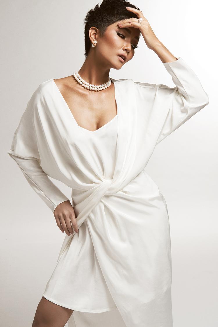 Bộ cánh thứ hai tạo điểm nhấn ở phần vải thắt chéo ở eo cùng ngực áo xẻ sâu đối xứng. Phom váy rộng mang đến sự thoải mái cho người mặc trong tiết trời mùa hè nhiệt đới oi ả.