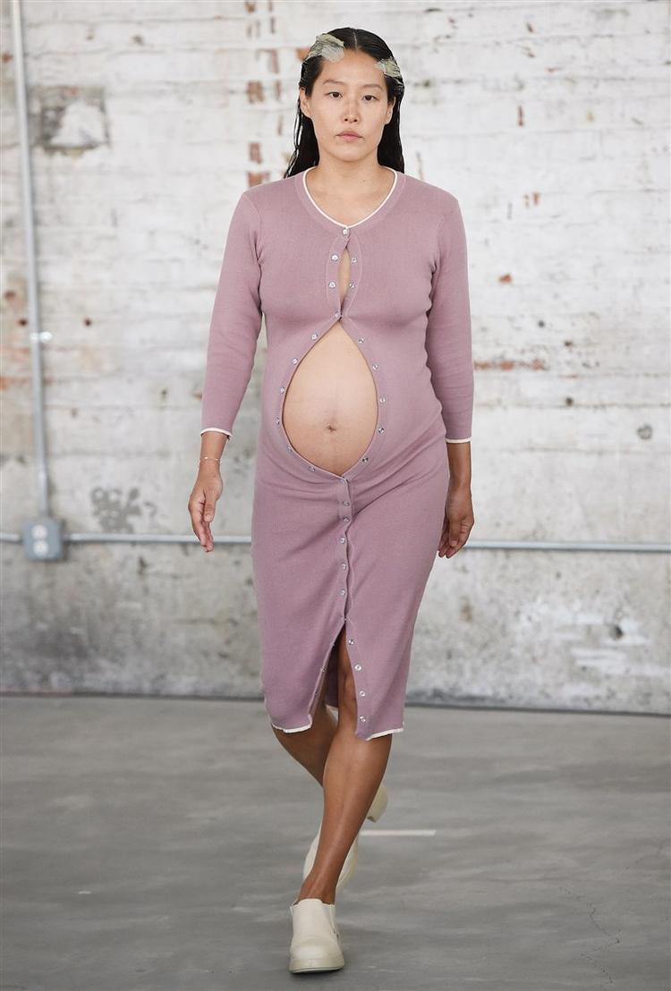 """Người mẫu Maia Ruth Lee mặc mẫu đầm cardigan màu hoa oải hương nhạt. Điểm gây ấn tượng cho khán giả ngày hôm đó chính là các nút váy cố ý không đóng lại hoàn toàn, để lộ phần bụng bầu """"quyến rũ"""" của cô."""