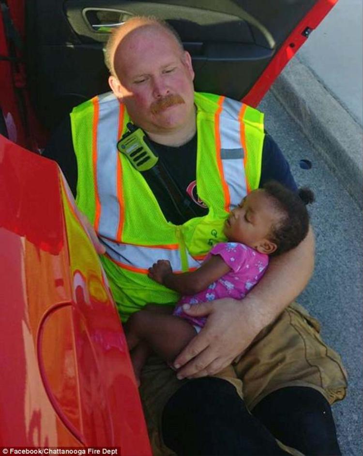 Bức ảnh người lính cứu hỏa ôm bé gái trong lòng sau vụ tai nạn được chia sẻ nhiều trên mạng xã hội.