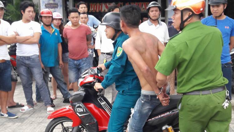 Nam thanh niên nghi ngáo đá bị công an khống chế để đưa về phường.