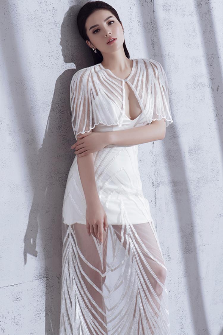 Váy ngắn cúp ngực táo bạo trở nên ấn tượng hơn bởi cách phối vải lưới kèm họa tiết kẻ sọc ánh kim hài hòa cùng màu váy.