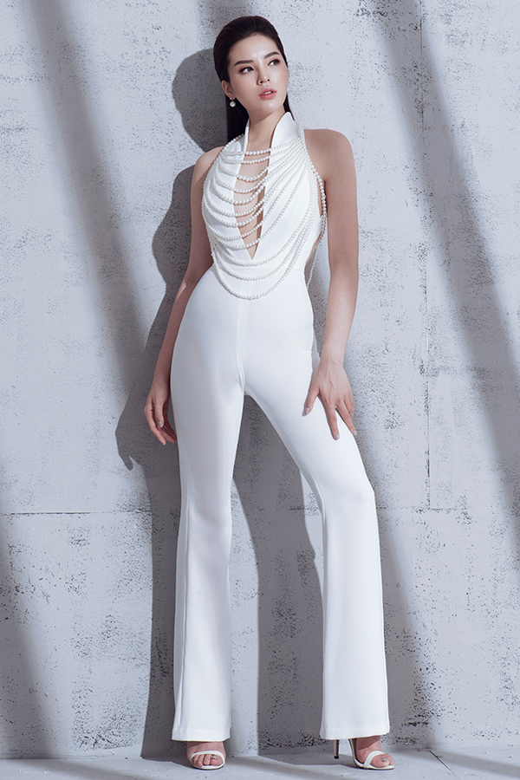Bộ jumpsuit với chi tiết xẻ sâu nhằm giúp người mặckhoe khéo vòng một. Trang phụccònthu hút ánh nhìn nhờchuỗi hạt giả ngọc traiđược đính liền trên thân áo.