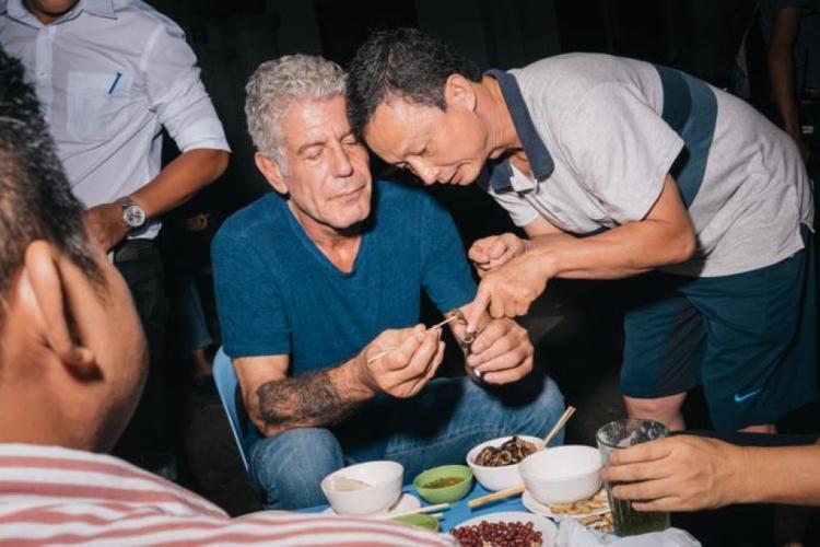 """Dù trong suốt sự nghiệp đứng bếp của mình, Bourdain từng phục vụ trong những nhà hàng danh tiếng, ông vẫn đặc biệt say mê với ẩm thực đường phố.""""Tôi thích ăn ở các quán ăn đường phố bình thường ở châu Á hay châu Mỹ La tinh. Tôi thích phở Việt Nam, cơm gà ở Singapore và taco ở Mexico. Tất cả đều ngon"""", vị đầu bếp nổi danh từng chia sẻ. Trong ảnh,một người dân Hà Nội hướng dẫn ông Bourdain trải nghiệm món ăn địa phương."""