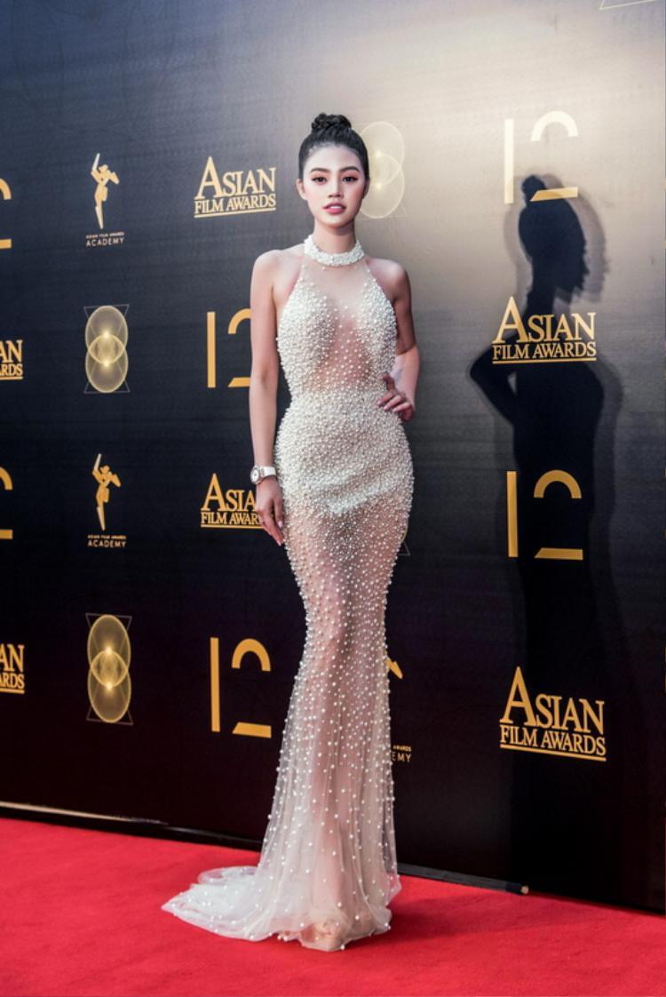 """Trong sự kiện""""Giải thưởng Điện ảnh châu Á lần thứ 12"""" vào hồi tháng 3/2018, Hoa hậu Jolie Nguyễn gây ấn tượng bởi vẻ đẹp ngọt ngào, quyến rũ. Cô diện chiếc đầm đính hở bạo được đính đá tinh tế của NTK Châu Phạm. Thiết kế """"lăng xê"""" gần như 80% cơ thể của chân dài."""