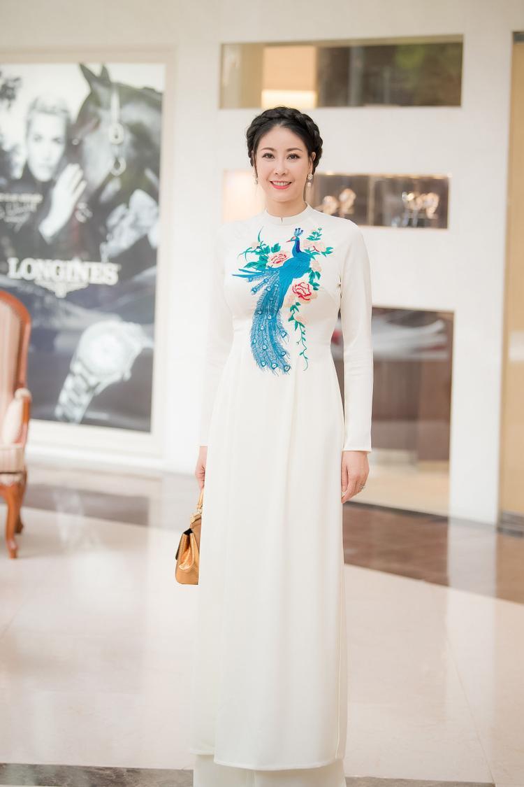 Hoa hậu Hà Kiều Anh chọn tà áo dài trắng cùng kiểu tóc tết vương miện mang đến một hình ảnh truyền thống nhưng cũng không kém phần hiện đại, sang trọng.