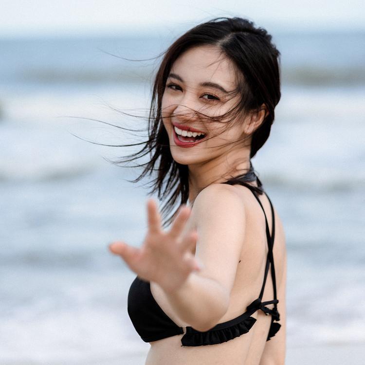 Diện trang phục bikini đen, nữ diễn viên khoe nụ cưởi tỏa nắng trên biển.
