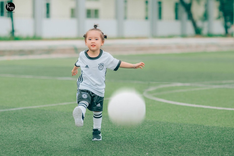 """Mẹ Như Anh hào hứng chia sẻ: """"Ngay sau khi có ý tưởng này, mình đã chuẩn bị cho bé 1 bộ quần áo và trái bóng. Đây cũng là lần đầu tiên con được mặc trang phục bóng đá và được đá trên sân cỏ nên con rất hào hứng""""."""