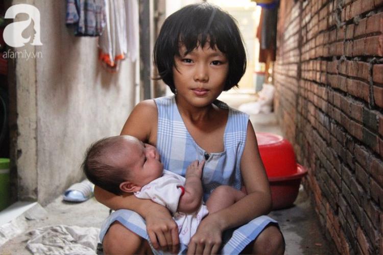 Hình ảnh cô bé nhỏ nhắn phải trông đứa em 2 tháng tuổi cho mẹ đi làm khiến không ít người xúc động.