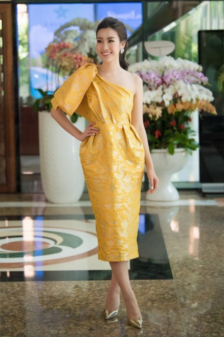 """Lần khác, đương kim Hoa hậu Việt Nam cực kì """"tỏa sáng"""" với thiết kế váy gấm vàng bất đối xứng, họa tiết rồng của Đỗ Mạnh Cường."""