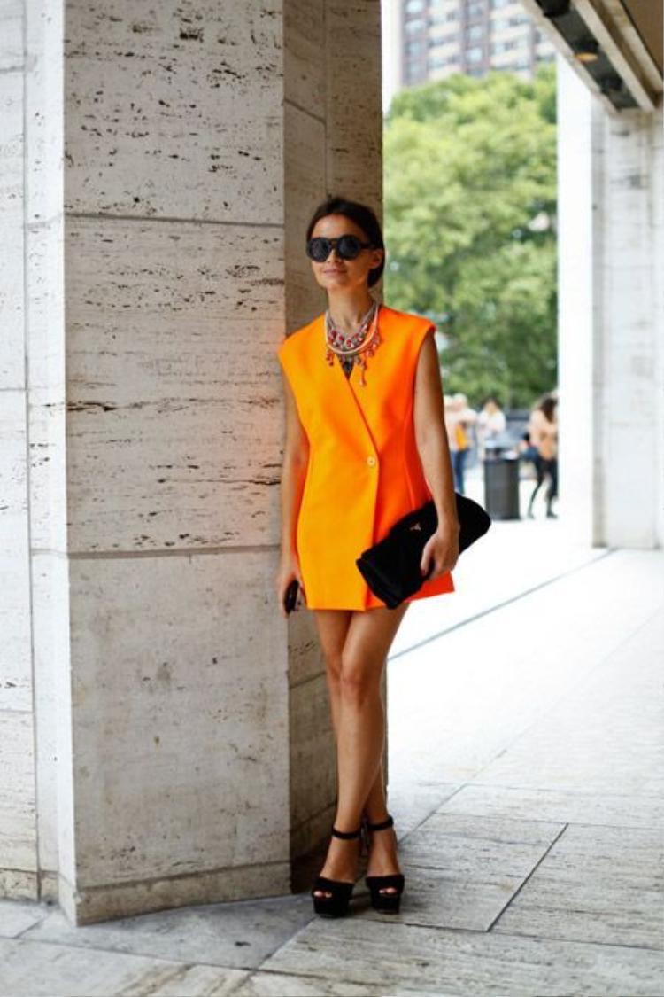 Chiếc đầm suôn vest không tay màu cam chói lọi được cô nàng khéo léo kéo hạ tông bằng phụ kiện màu đen như kính mát, giày và túi.