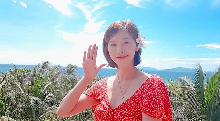 Trong bức ảnh đầu tiên, nữ diễn viên mặc một chiếc váy màu đỏ rực, tóc cài hoa và giơ tay chào người hâm mộ ở mảnh đất hình chữ S.