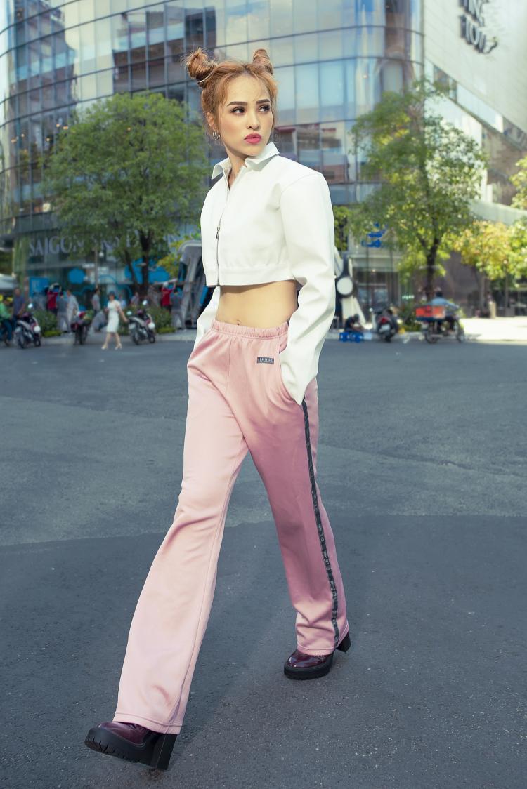 """Chân dài để lộ """"vòng eo con kiến"""" trong bộ crop-top trắng, kết hợp với quần ống suông màu hồng phấn điệu đà."""
