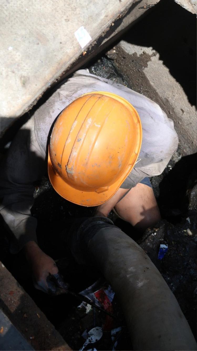 Công nhân vệ sinh phải vất vả ngụp trong cống để vớt rác, thông cống