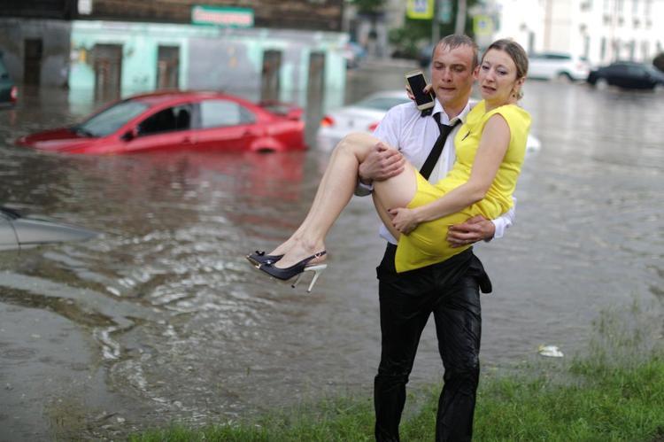 Người phụ nữ được chàng trai đưa lên bờ một cách an toàn. Tình trạng nước ngập đường phố ởNizhny Novgorod là do hệ thống thoát nước tại đây hoạt động kém.