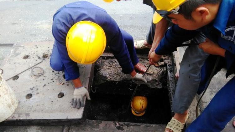 Các công nhân nạo vét cống thoát nước