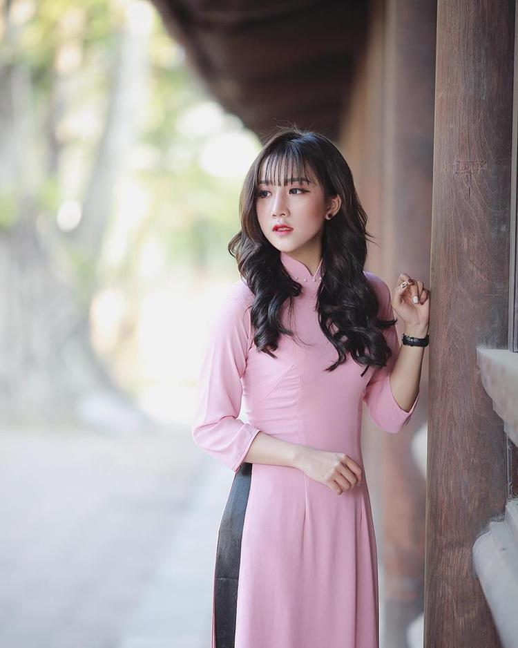 Nữ sinh nền nã với áo dài hồng.